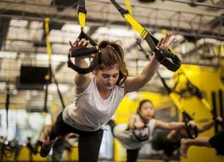 یک خانم در حال انجام ورزش تی آر ایکس