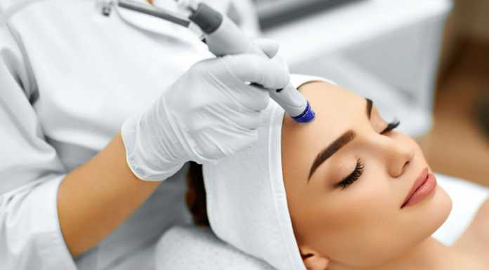 یک خانم در حال از بین بردن موهای زائد صورت با دستگاه لیزر