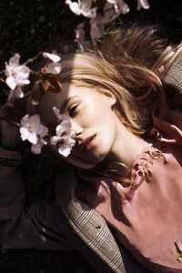 دختری که در میان گلها دراز کشیده است