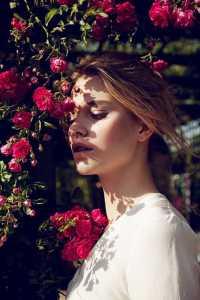 دختری در کنار یک بوته گل صورتی