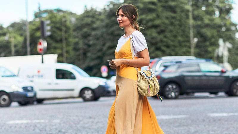 خانمی با لباس های چند لایه در حال راه رفتن در خیابان