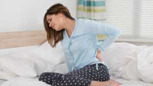خانمی روی تخت خواب با کمردرد