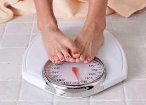 فردی در حال وزن کردن خود بر روی ترازو