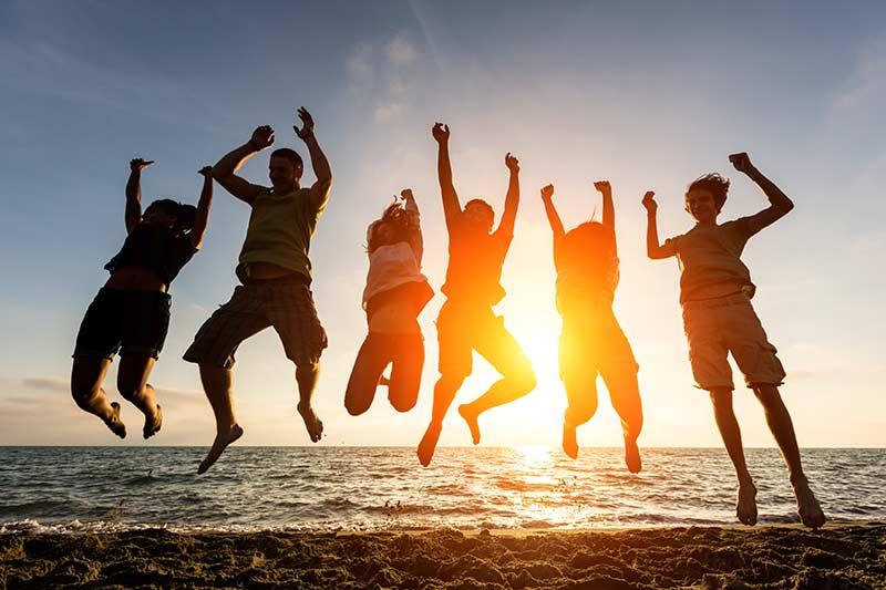چند نفر در کنار دریا که به بالا پریده و شادی می کنند
