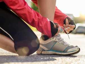 ورزش کار خانم در حال بستن بند کفش