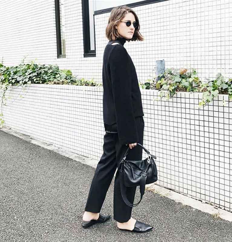 یک خانم با بلوز و شلوار و عینک و کیف و کفش مشکی