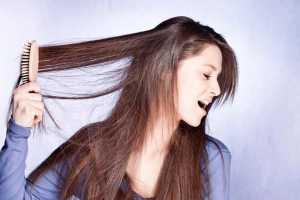 یک خانم در حال برس کشیدن موهای بلندش