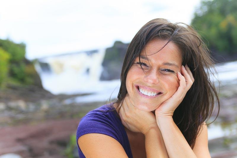 یک خانم با موهای مشکی و تی شرت بنفش در حال خندیدن