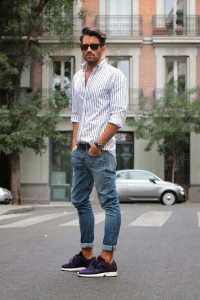 یک آقا با عینک آفتابی و پیراهن سفید راه راه و شلوار جین