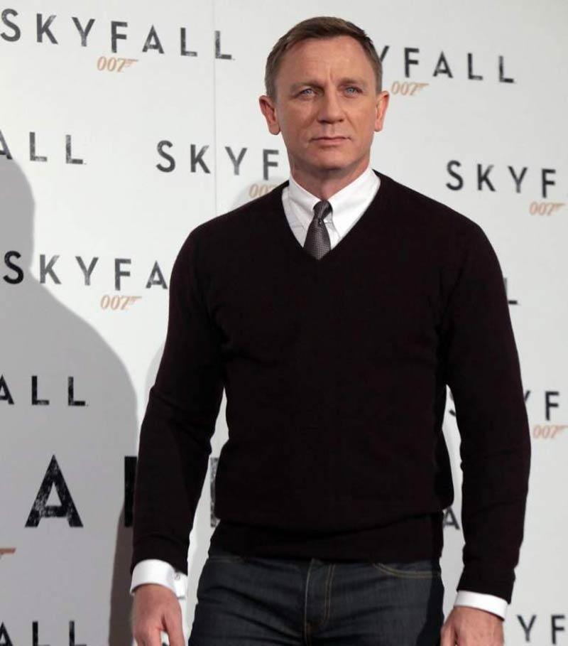 یک مرد با پلیور یقه هفت مشکی و پیراهن مردانه سفید و کراوات