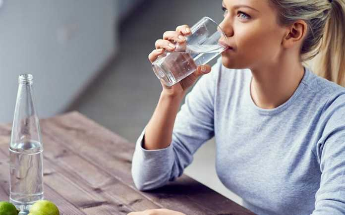 یک خانم در حال نوشیدن آب و تاثیر نوشیدن آب بر لاغری