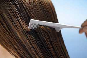یک خانم در حال شانه کردن موهای بلندش