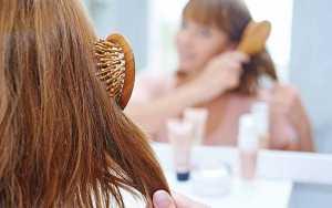 یک خانم در حال برس کشیدن موهایش