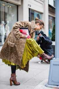 یک خانم با بوت پاشنه بلند قهوه ای و لباس زرئ