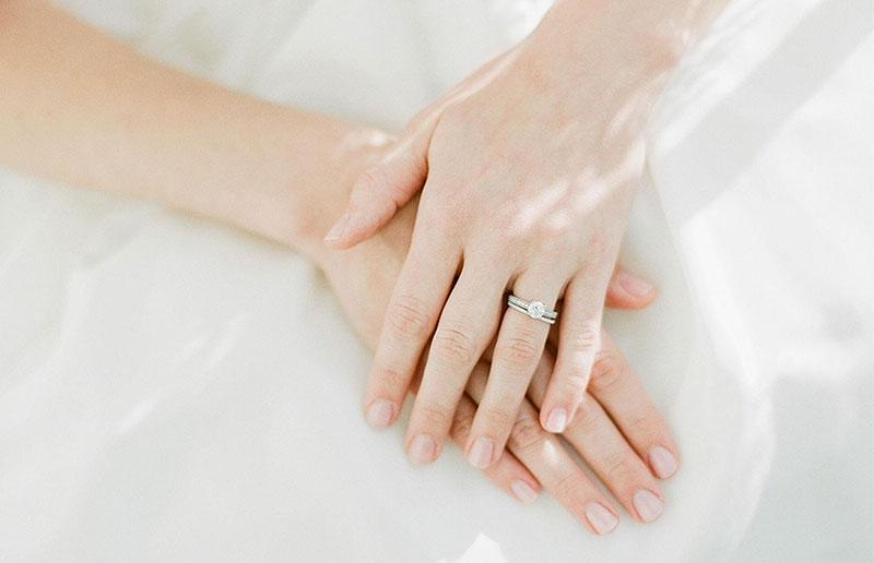 دست های یک خانم با ناخن های کوتاه و انگشتر