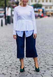 یک خانم با پیراهن سفید و شلوار کوتاه جین
