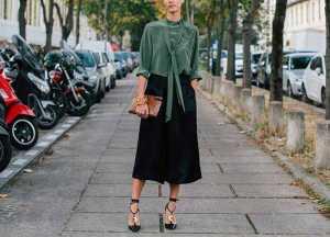 یک خانم با شومیز سبز و شلوار کوتاه گشاد مشکی و کفش پاشنه بلند