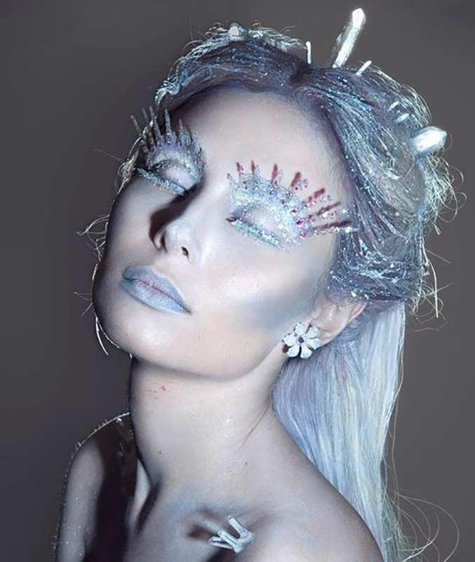 آرایش یک خانم برای هالووین که به صورت ملکه یخی بوده و صورت خود را سفید و آبی کرده است