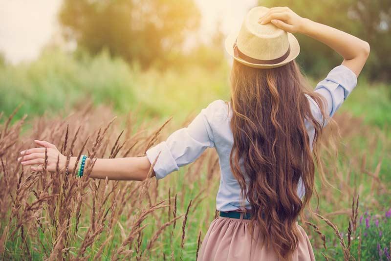 یک خانم با موهای بلند و کلاه در طبیعت