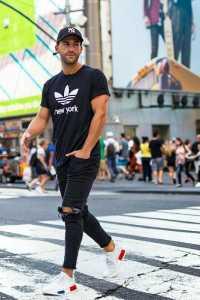 یک آقا در خیابان با تی شرت و کلاه و شلوار جین مشکی پاره