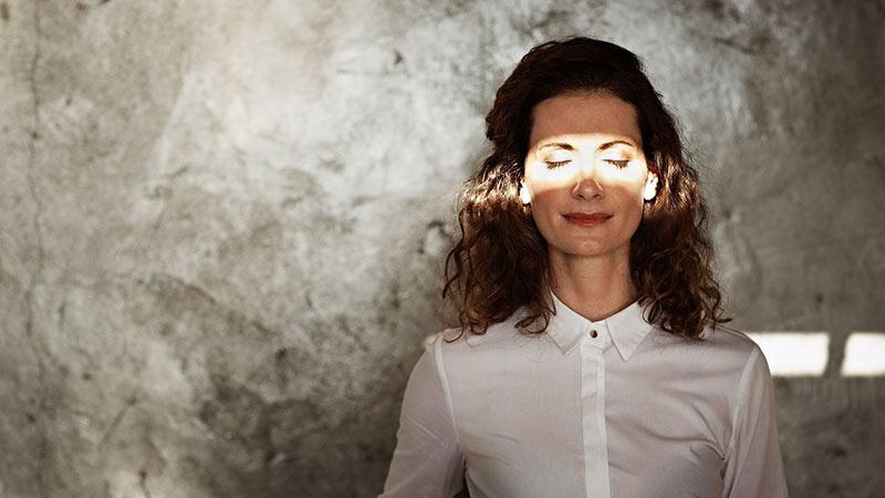 یک خانم با موهای تیره که نور بر روی چشمانش افتاده است