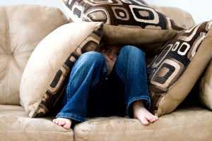 یک پسر بچه که زیر بالشت های مبل پنهان شده