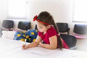 یک دختر بچه با موهای بافته شده مشکی در حال کشیدن نقاشی