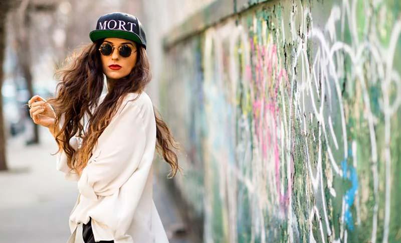 یک خانم با موهای قهوه ای فر بلند و عینک آفتابی و کلاه کپ مشکی و پیراهن سفید
