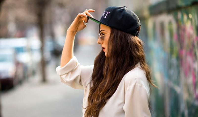 نیم رخ یک خانم با موهای قهوه ای فر بلند و عینک آفتابی و کلاه کپ مشکی و پیراهن سفید