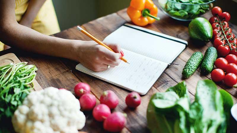 دست یک خانم در حال نوشتن کالری سبزیجات