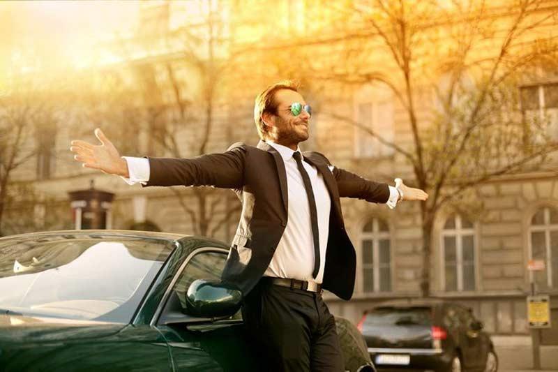 یک آقا با کت و شلوار و عینک آفتابی با دست های باز تکیه داده به ماشین