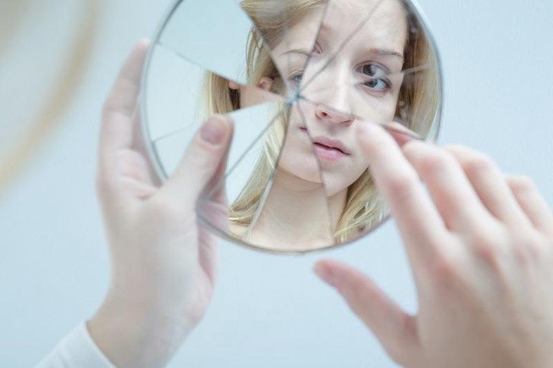 یک خانم در حال نگاه کردن به خود در آیینه شکسته