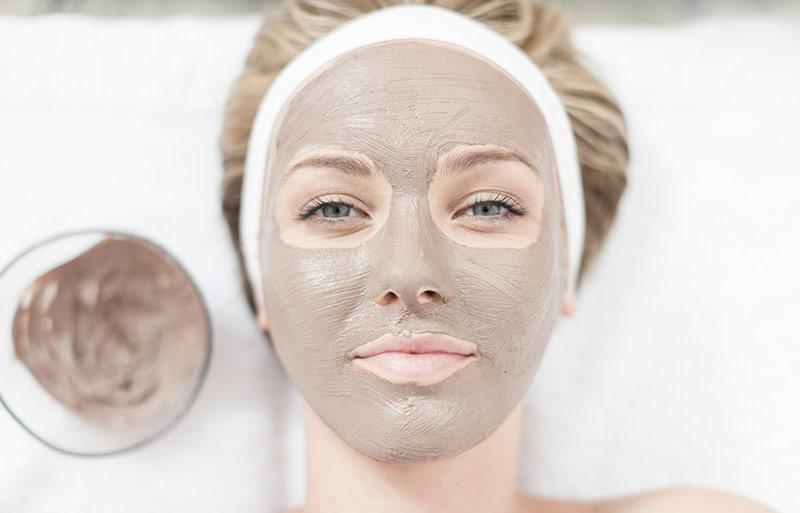 صورت یک خانم در حال استفاده از ماسک خاک رس