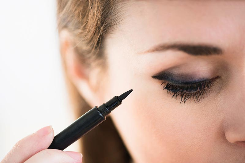بخشی از صورت یک خانم در حال کشیدن خط چشم