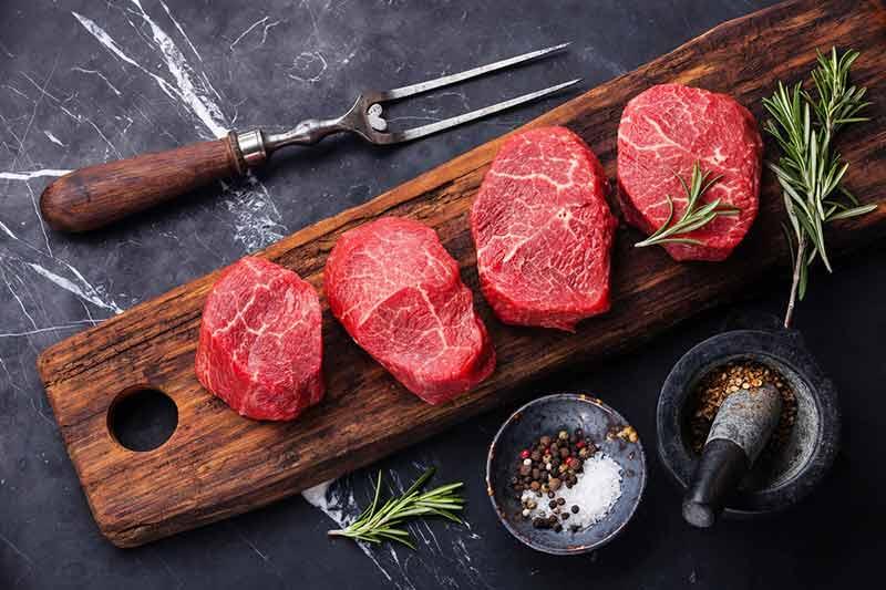 یک ظرف چوبی با چهار تکه گوشت قرمز