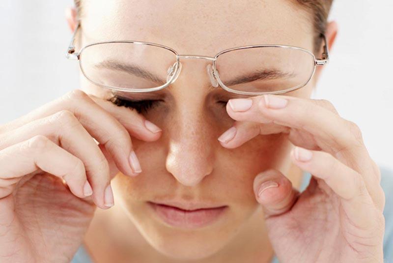 یک خانم با استرس در حال مالش چشم های خود