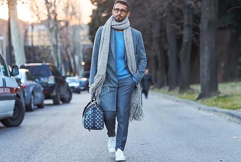 یک آقا با شال گردن و کت و کیف و شلوار طوسی