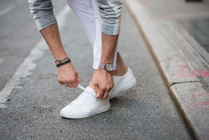 یک آقا در حال بستن بند کفش سفید مردانه