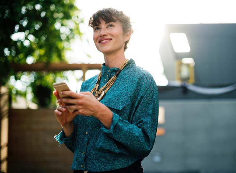 یک خانم با لبخند در حال استفاده از موبایل