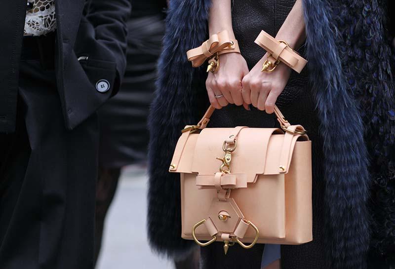 دست های یک خانم با کیف و دستبند چرم کرم