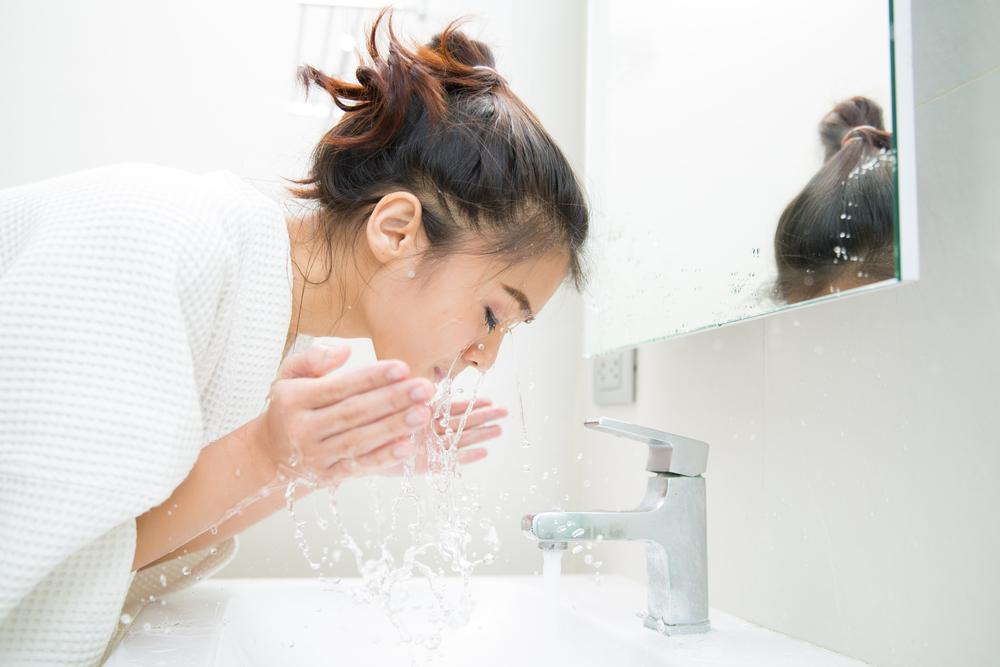 خانمی در حال شستشوی پوست صورت