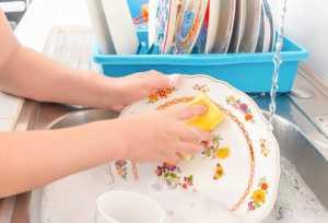 دست های یک خانم در حال شستن ظرف