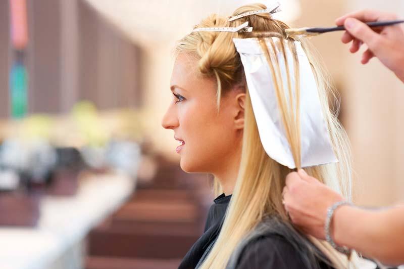 یک خانم در حال رنگ کردن موهای بلوندش