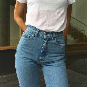 نیمی از بدن یک خانم با شلوار جین فاق بلند و تی شرت سفید