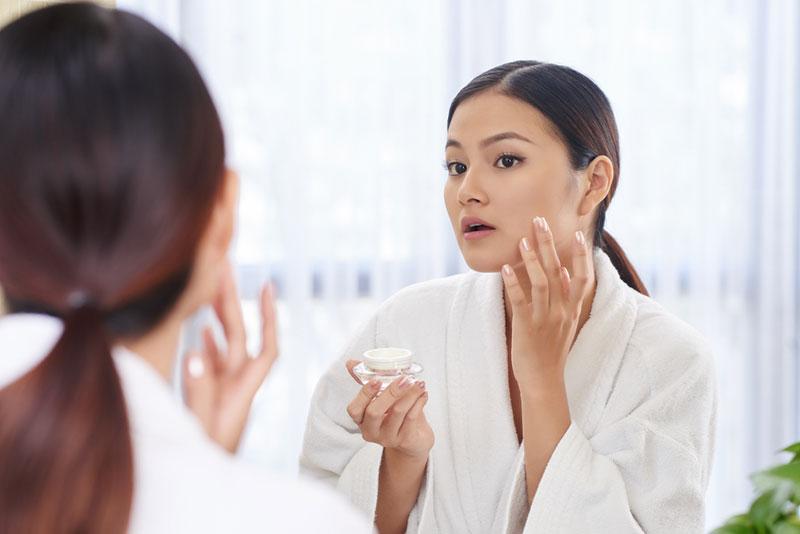 یک خانم در حال استفاده از کرم های پوست