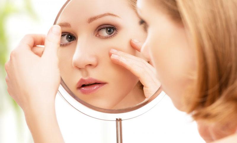 یک خانم در حال نگاه کردن به پوست خود در آیینه