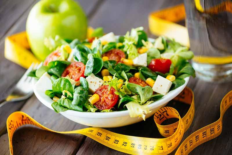 یک ظرف سبزیجات کنار یک عدد متر زرد
