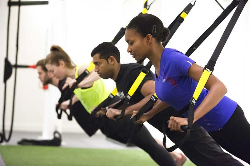 چند خانم و آقا در حال انجام ورزش تی آر ایکس