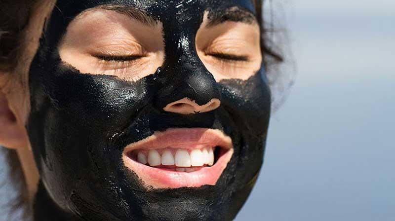 یک خانم که به صورت خود ماسک زغال زده است
