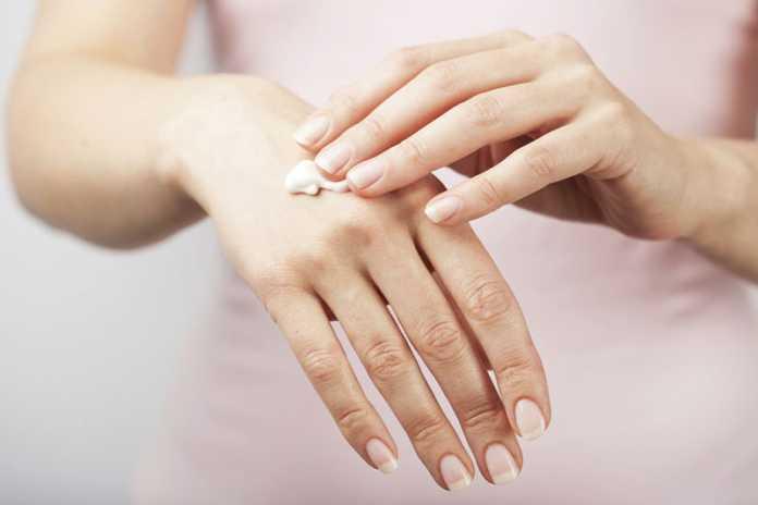 یک خانم در حال استفاده از کرم مرطوب کننده برای از بین بردن خشکی دست